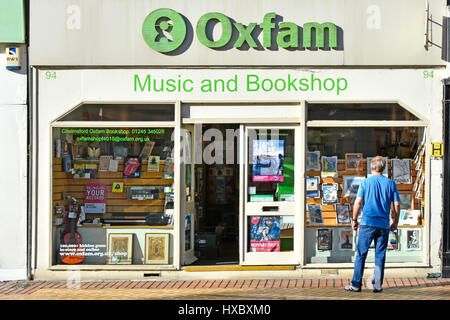 Town centre shopping street Oxfam charity music store & bookshop shop front with man window shopping Chelmsford - Stock Photo
