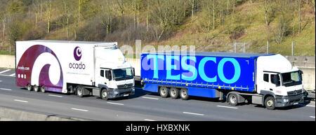 Ocado online supermarket distribution lorry overtaking Tesco supermarket store distribution truck on M25 UK motorway - Stock Photo
