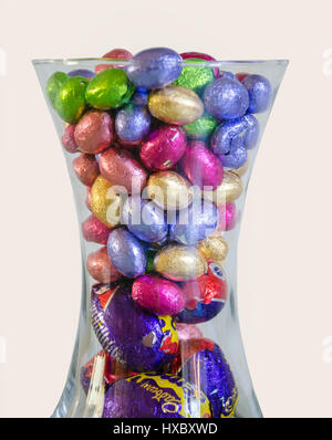 Mini chocolate Easter eggs wrapped in brightly coloured foil wrappings in a glass vase. - Stock Photo