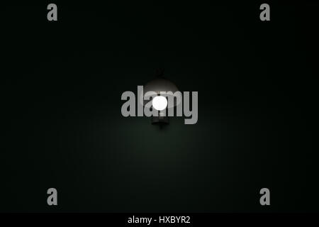 Abstract background with an old dirty lamp glowing in the dark with a  flat green background - Stock Photo
