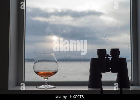 Brandy snifter glass in window with binoculars - Stock Photo