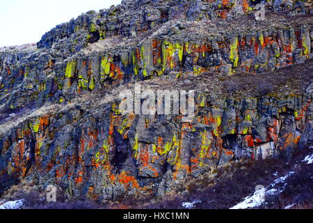 Medicine Lodge rocks with lichen growing in green, yellow, red, and orange on them. Lava rock walls - Stock Photo