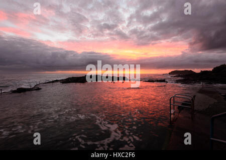 Fiery sunrise over Kiama rock pool, Kiama, Illawarra Coast, New South Wales, NSW, Australia - Stock Photo