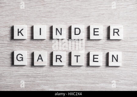Alphabet letters on wooden pieces collected to word kinder garten - Stock Photo
