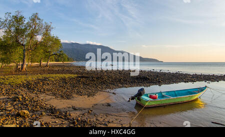 A small Green and Blue wooden boat tied up on ABC Beach on Tioman Island, Malaysia as the sunsets and the tide comes - Stock Photo