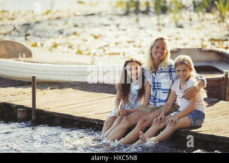 Portrait happy mother and daughters on dock splashing feet in lake - Stock Photo