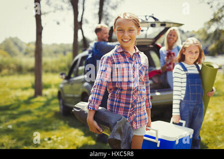 Portrait smiling family unloading camping equipment from car - Stock Photo