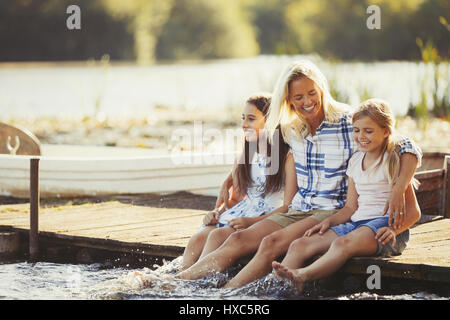 Smiling, affectionate mother and daughters on dock splashing feet in lake - Stock Photo
