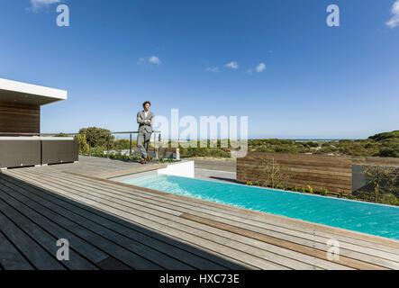 Businessman on sunny modern, luxury patio with infinity pool - Stock Photo