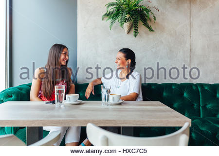Two happy women talking in cafe. Aged woman and her adult daughter drinking coffee at cafe. Mothers day. - Stock Photo