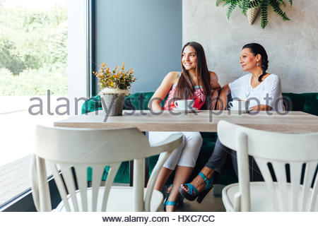 Two happy women in cafe. Aged woman and her adult daughter drinking coffee and looking through the window in a cafe. - Stock Photo