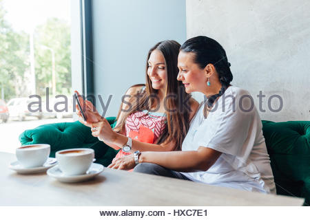 Mother and daughter women using a mobile phone in a cafe - Stock Photo