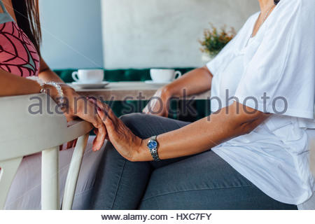 Mother and daughter women holding hands affectionate in a cafe - Stock Photo
