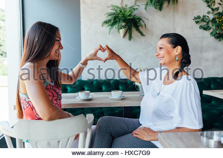 Mom and daughter making a heart with hands. Love coffee. - Stock Photo