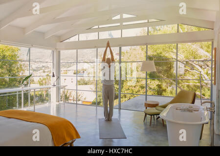 Mature man practicing yoga with hands clasped overhead in luxury bedroom - Stock Photo