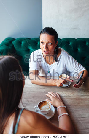Surprised mother showing her daughter something on a mobile phone in a cafe - Stock Photo