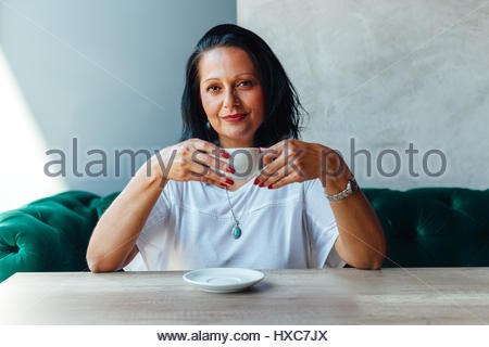 Portrait of beautiful middle aged woman in a cafe - Stock Photo
