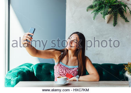 Beautiful young woman making selfie in a cafe - Stock Photo