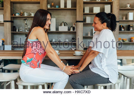 Two beautiful happy women in a cafe - Stock Photo