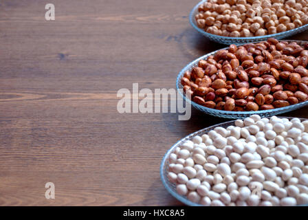 Pulses in a bowl on a wooden table for bacgrounds (Haricot beans, kidney bean and chickpea) - Stock Photo