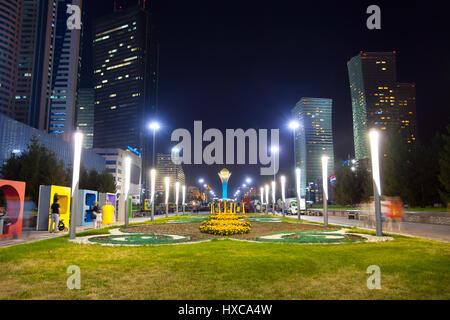Night in Astana - capital of Kazakhstan. In the center is the monument Baiterek. People walk along the boulevard. - Stock Photo