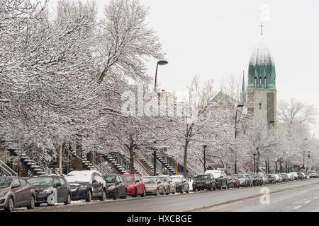 Montreal, Canada - 25 March 2017: Christophe-Colomb Street and Paroisse Saint-Arsene church in winter - Stock Photo