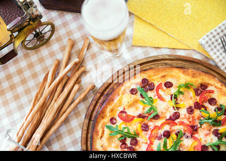 Tasty pizza with cheese, tomato and meat, with glass of beer on served table with plaid tablecloth - Stock Photo