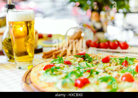 Tasty pizza with glass of beer, on served table - Stock Photo