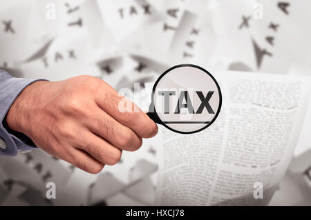 Business hand looking Tax word using magnifying glass on the paper - Stock Photo