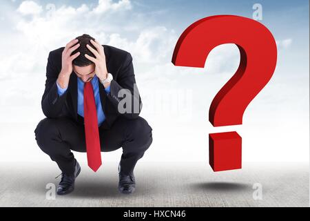 Digital composite of Worried businessman with 3d question mark on his side - Stock Photo