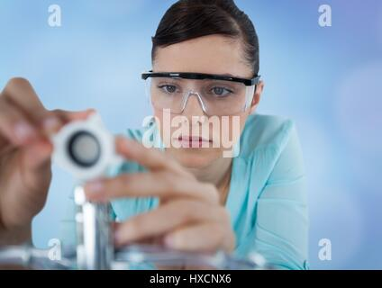 Digital composite of Close up of woman with electronics against blurry blue background - Stock Photo