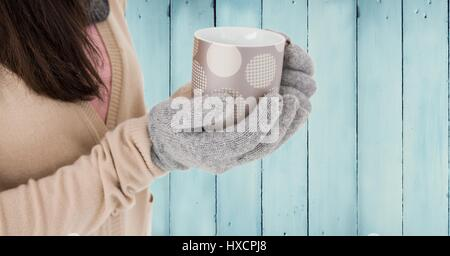 Digital composite of Close up of woman with polka dot mug against blue wood panel - Stock Photo