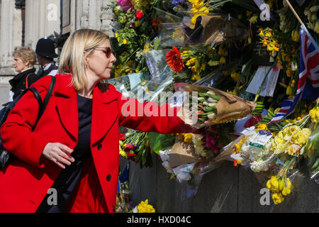 Westminster London, UK. 27th Mar, 2017. Judy Mitchem leaves flowers of tributes on the railings of the Palace of - Stock Photo