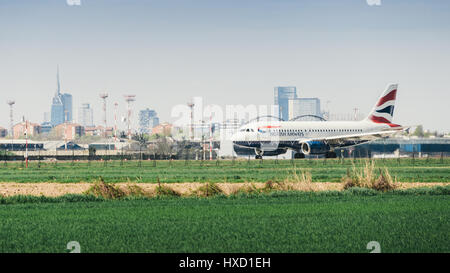 A British Airways commercial airplane takes off from Milan's Linate airport. Linate is a main hub for Alitalia servicing - Stock Photo