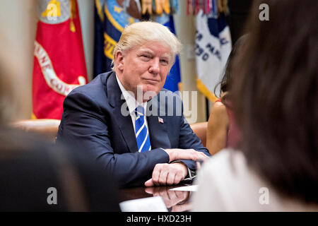 Washington, USA. 27th Mar, 2017. U.S. President Donald Trump listens while meeting with women small business owners - Stock Photo