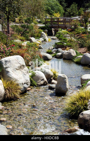 ... Close Up Of A Beautiful, Shallow Stream Running Over Rocks In A Garden  Setting With