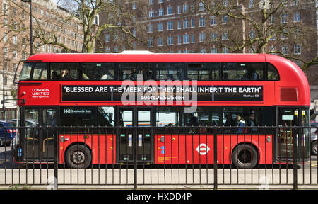 London, UK. One of the New Routemaster red buses introduced in 2012. It bears a biblical poster 'Blessed are the - Stock Photo