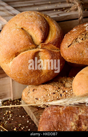 closeup of an assortment of different bread rolls and some wheat ears on a rustic wooden table - Stock Photo