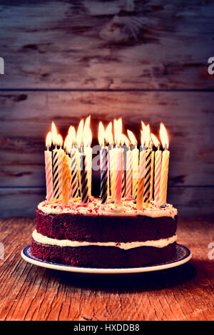 a cake topped with some lit candles before blowing out the cake, on a rustic wooden table, against a blue wooden - Stock Photo