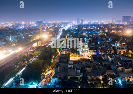 Cityscape of Noida Delhi at night with lights and under construction buildings - Stock Photo