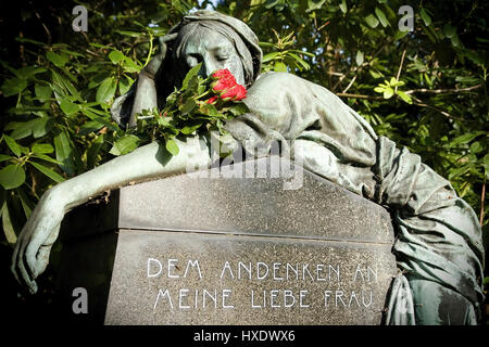 Statue of a woman with roses on the Ohlsdorfer cemetery in Hamburg, statue of a woman with roses on the village - Stock Photo