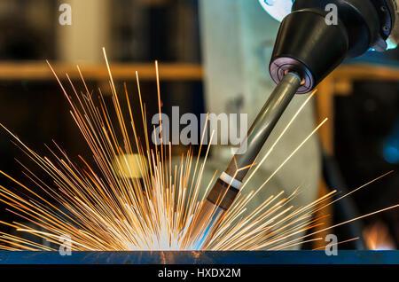 Close up robot is welding metal part in factory - Stock Photo