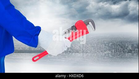 Digital composite of Mechanic arm with wrench against blurry skyline - Stock Photo