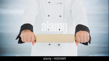Digital composite of Chef with rolling pin against blurry grey wood panel - Stock Photo