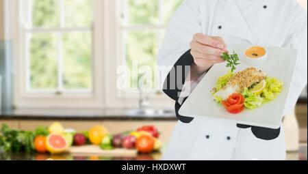 Digital composite of Chef with plate of food against blurry kitchen with vegetables - Stock Photo