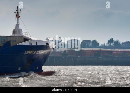 The container ship Henrike Schepers steaming upriver on the River Thames in the UK. - Stock Photo