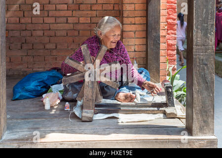 Bhaktapur, Nepal - 20 March 2015: Old woman spinning wool - Stock Photo