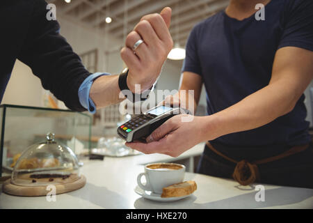 Cropped image of customer paying with NFC technology on smart watch in coffee shop - Stock Photo