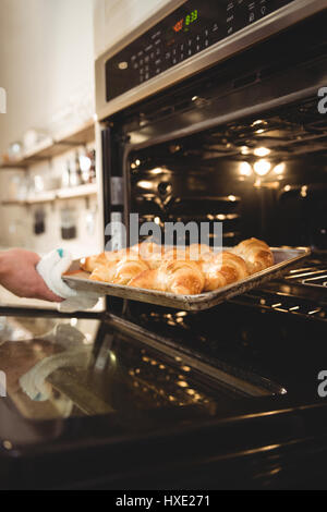 Cropped image of man taking out tray of freshly baked croissants from oven in coffee chop - Stock Photo