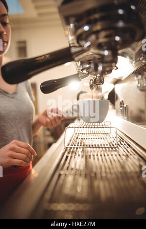Cropped image of female barista making coffee using espresso machine in cafe - Stock Photo